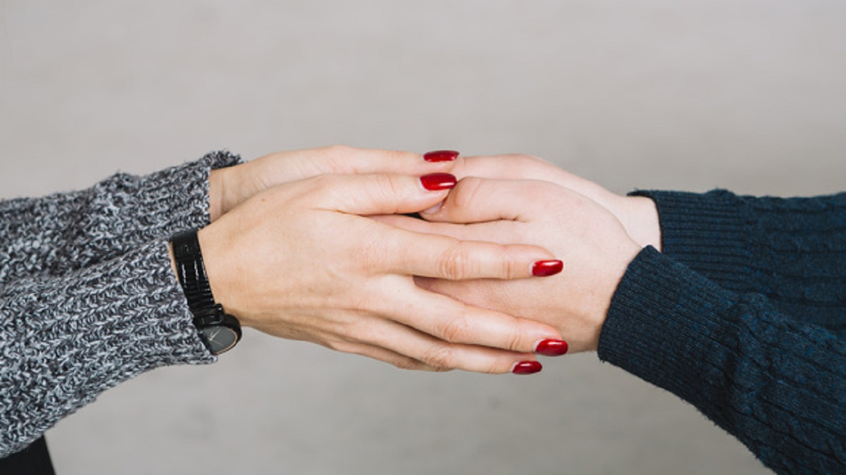 cropped-image-female-psychologist-holding-her-client-s-hands-against-gray-backdrop_23-2148036684