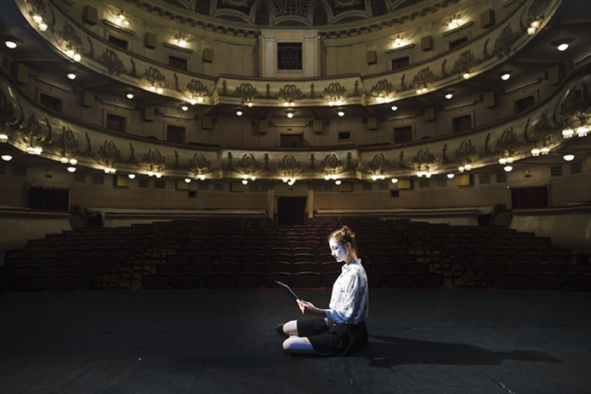 side-view-female-mime-reading-manuscript-empty-auditorium_23-2147891801