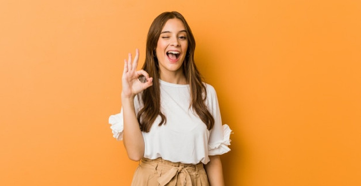 young-caucasian-woman-winks-eye-holds-okay-gesture-with-hand_1187-23382