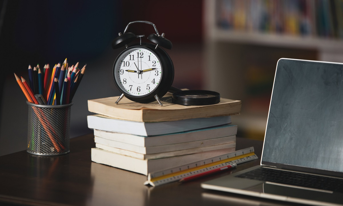 Book,laptop,pencil,clock on wooden table in library,education le